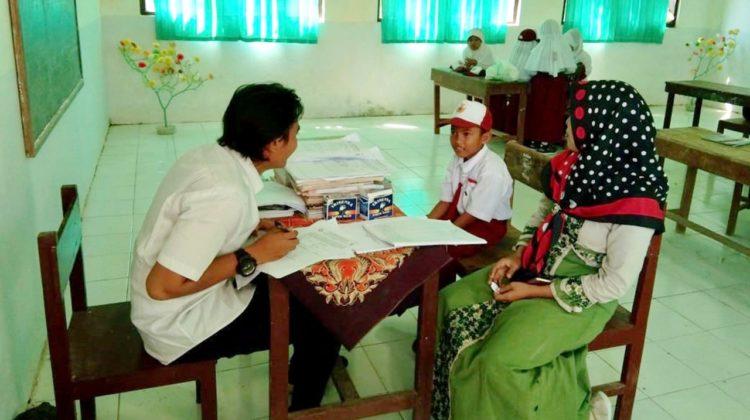 Tim Abdimas sedang mengukur literasi kemampuan membaca siswa yang di damping orang tuanya di SDN Talaga 2