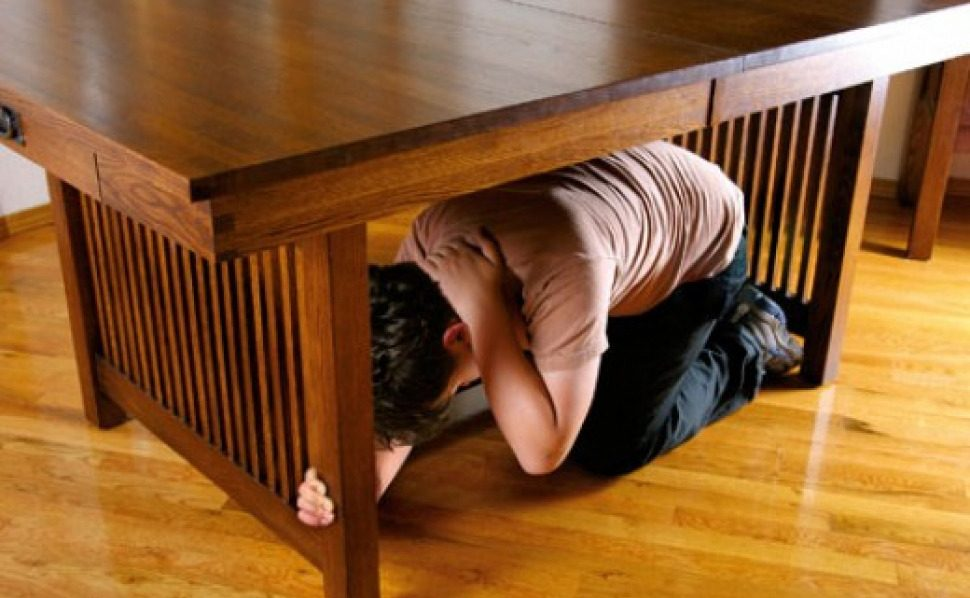 Ilustrasi melindungi diri di bawah meja saat terjadi gempa bumi