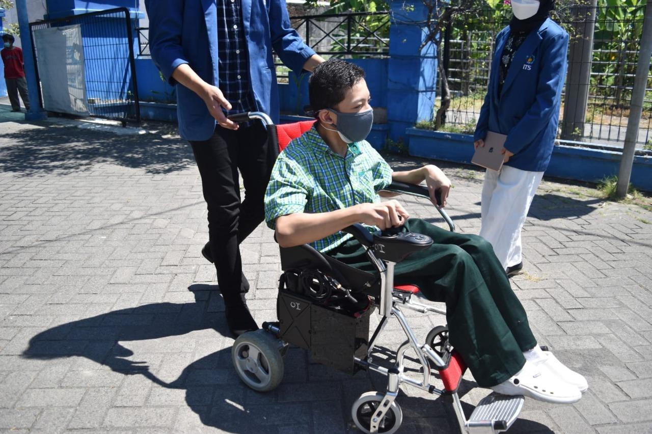Salah satu siswa SLB YPAC Surabaya saat mencoba menggunakan Kursi Roda Elektrik dibantu oleh tim KKN Abmas ITS