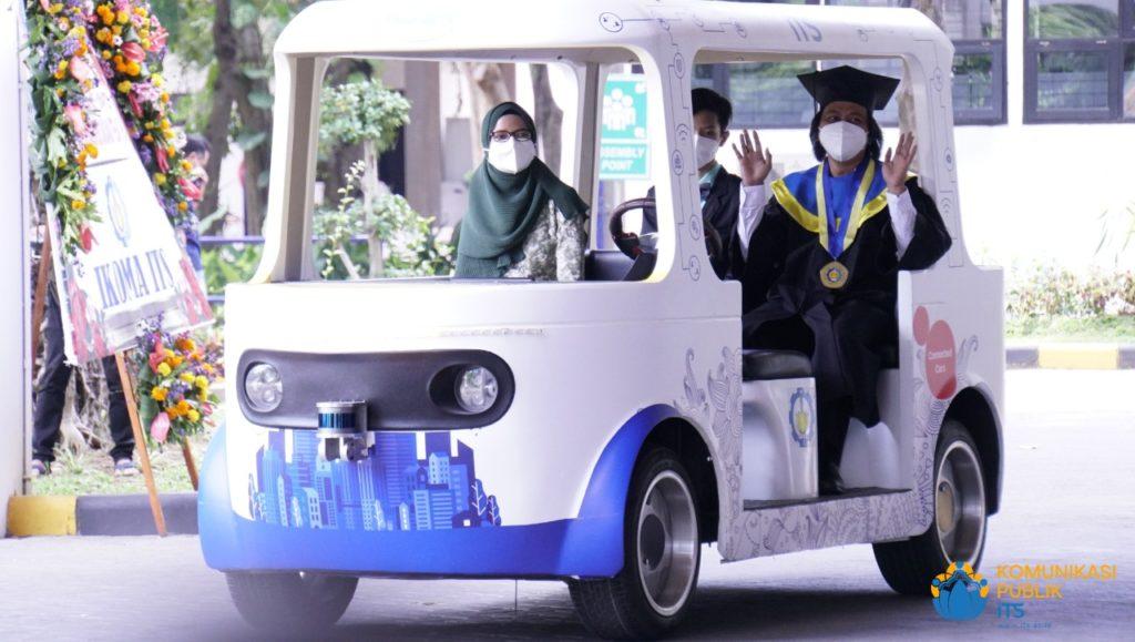 Dr Rudi Dikairono ST MT (bertoga), wisudawan program doktor dari program studi Teknik Elektro FTEIC yang datang bersama istri dan putranya mengendarai mobil listrik tak berawak i-Car