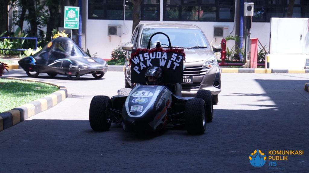 Mobil yang membawa wisudawan program doktor Teknik Mesin ITS, Dr Ir Witantyo MEngSc, saat menuju depan Gedung Rektorat ITS dengan iringan mobil Tim Sapuangin ITS